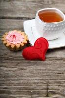 kopje thee, cake en rood hart foto