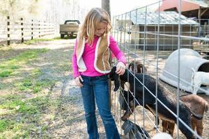 jong meisje speelt met geit foto