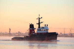 rivier sleepboot, ochtendnevel foto