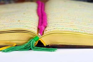 koran met rozenkrans bidparels in kleuren en gouden bladzijden