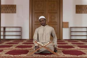 moslim man in dishdasha leest de koran