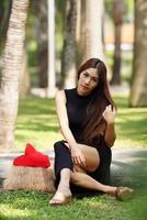 mooie Aziatische dame in zwarte jurk, die zich voordeed in het park foto