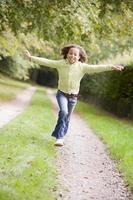 jong meisje dat op een weg loopt die in openlucht glimlacht foto