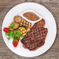 gegrilde steaks, gebakken aardappelen en groenten op witte plaat