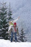 man geeft vriendin ritje op de rug op een besneeuwde heuvel foto