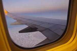 vleugel van het vliegtuig verlicht door de zonsondergang