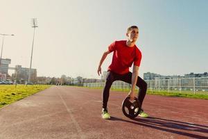 atletische man heft gewichten op foto