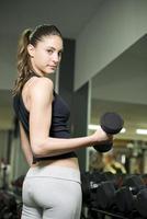 jonge vrouw tillen gewichten foto