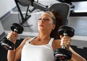 vrouw tillen gewichten in de sportschool foto