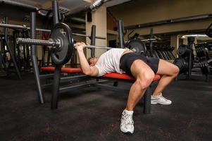 jonge man doet bench press training in de sportschool foto