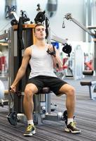 man uitoefenen op gym machine foto