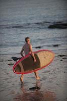 man met zijn paddle board op het strand bij zonsondergang
