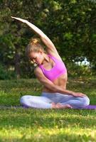 meisje doet yoga en gymnastiek op het gras foto