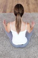 mooie jonge vrouw die yogaoefeningen thuis doet.