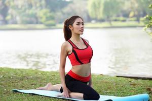 jonge mooie vrouw die yogaoefeningen in park doet foto