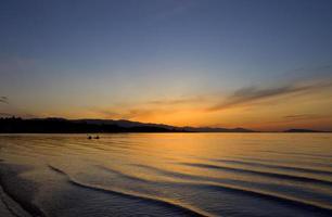 silhouet van kajaks bij zonsondergang
