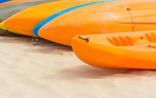 kleurrijke kajaks ordelijk aanmeren op het strand foto