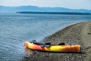 oranje en gele kajak met roeiriemen aan de kust foto