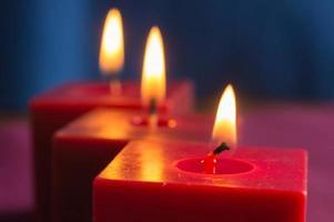 rij van drie brandende rode kaarsen foto