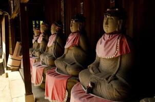 rij stenen beelden buiten een Japanse tempel foto