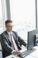 volwassen zakenman werken op de computer in kantoor foto