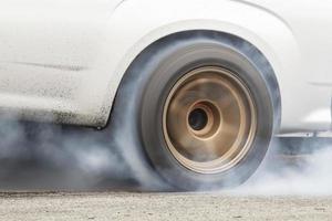 auto verbrandt rubber van zijn banden voor de race foto
