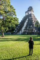 jong meisje overweegt Maya-ruïnes in Tikal, nationaal park. tr foto