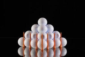 piramide van golfballen op een zwarte achtergrond foto