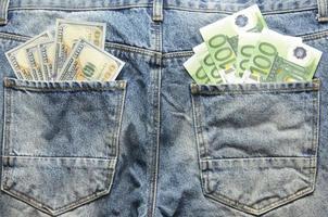 euro- en dollarbankbiljetten in jeans achterzakken foto