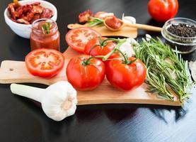 ingrediënten. verse tomaten, zongedroogde tomaten, tomatensaus en kruiden. foto