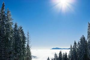 berglandschap met pieken vallende sneeuw en wolken foto