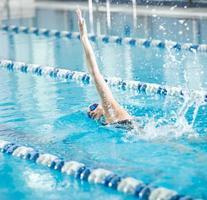 jong meisje in bril zwemmen borstcrawl slag stijl foto