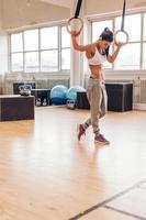 doordachte jonge vrouw die gymnastiek- ringen houdt bij gymnastiek foto