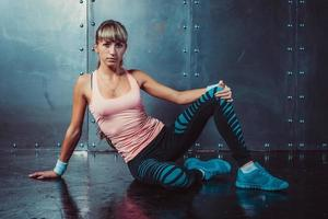sportieve fitness vrouw zitten en ontspannen op de vloer foto