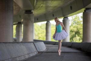 sierlijke ballerina die dansoefeningen doet op een betonnen brug