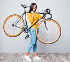 vrouw met fiets op schouder foto