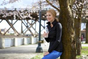 atletische jonge vrouw rust tegen boom foto