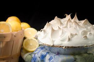 mand met citroenen met citroen meringue pie. foto