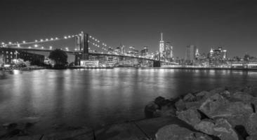 zwart-wit foto van de waterkant van Manhattan in de nacht.
