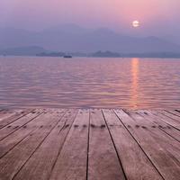 plank bord met meer in zonsondergang als achtergrond foto
