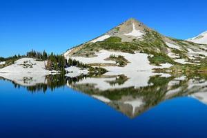 besneeuwde bergen en alpine meer met reflectie foto