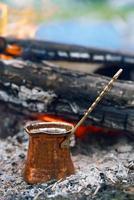 koffie zetten in de open haard tijdens kamperen of wandelen foto