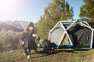 man camping drinken koffie in de buurt van tent glimlachend gelukkig buiten in