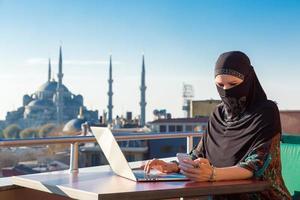 traditioneel geklede moslimvrouw die aan computer werkt foto
