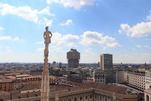 kathedraal standbeeld en uitzicht op Milaan stadsgezicht met torre valesca