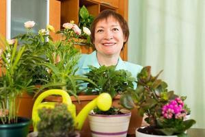 vrouwelijke volwassen tuinman met planten glimlachen foto