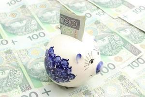 spaarvarken en geld op hoop bankbiljetten foto