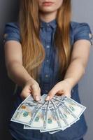 fan van 100 dollar biljetten in handen van de vrouw foto
