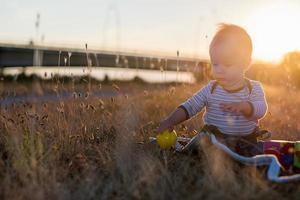 jongetje heeft plezier buiten op zonsondergang