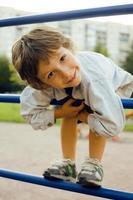 kleine schattige jongen op speelplaats buiten foto